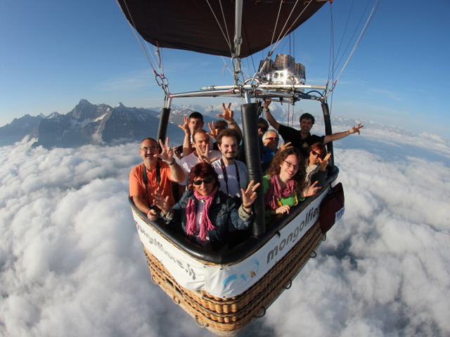 cesta di una mongolfiera con persone a bordo, felici di esser più in alto delle nuvole