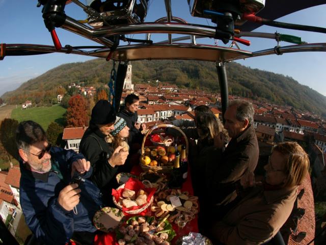 persone fanno merenda dentro al cesto di una mongolfiera in volo