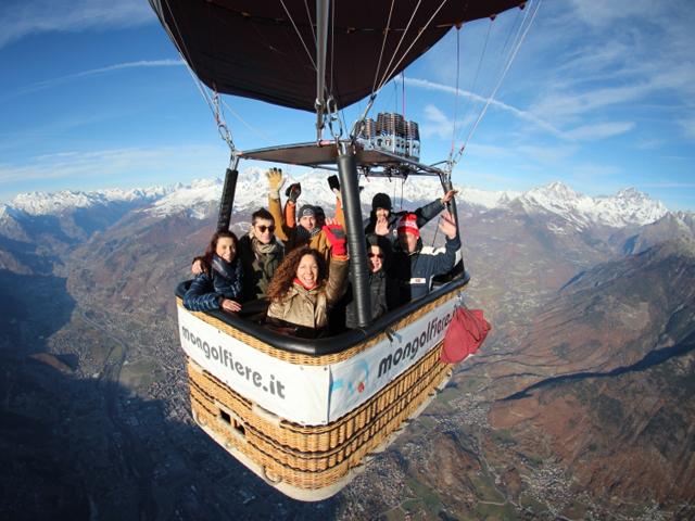 persone salutanto dal cesto di una mongolfiera che sorvola delle montagne alte con la cima innevata