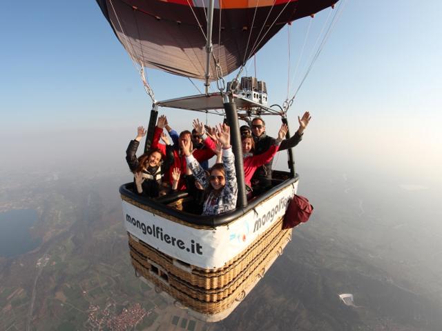 alcune persone dentro al cesto di una mongolfiera salutano felici