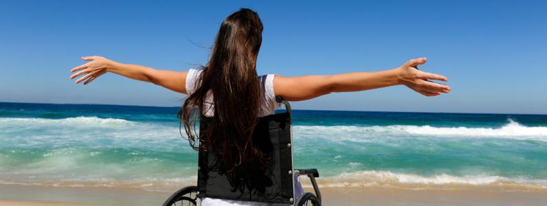 Donna in sedia a rotelle spalanca le braccia in riva al mare