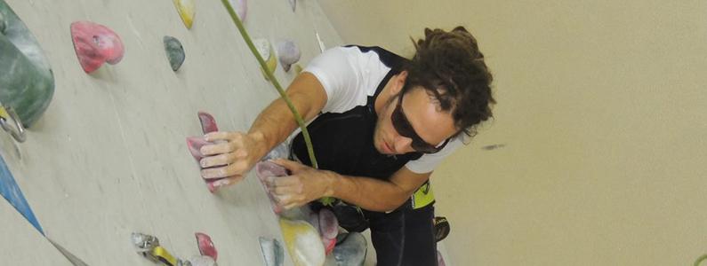 Simone Salvagnin esperto ipovedente di arrampicata sportiva mentre scala una parete attrezzata in palestra
