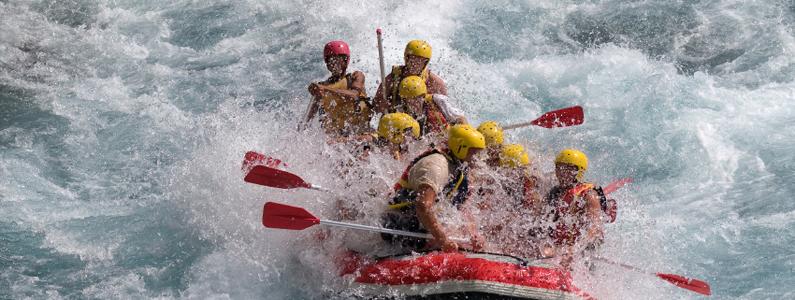 Otto persone in un gommone fanno rafting in mezzo alle rapide di un fiume
