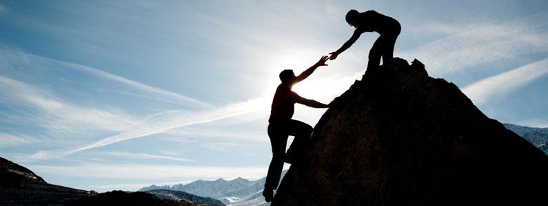 Un uomo tende la mano ad un altro uomo per aiutarlo a salire sopra una roccia