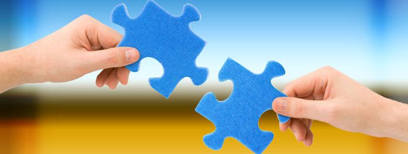 Due mani che tengono due pezzi di puzzle che stanno per essere attaccati