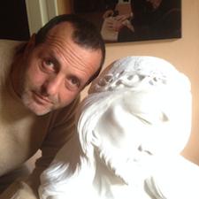 Primo piano di Felice Tagliaferri a fianco di una sua scultura