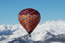 vista di una mongolfiera che sorvola delle montagne innevate