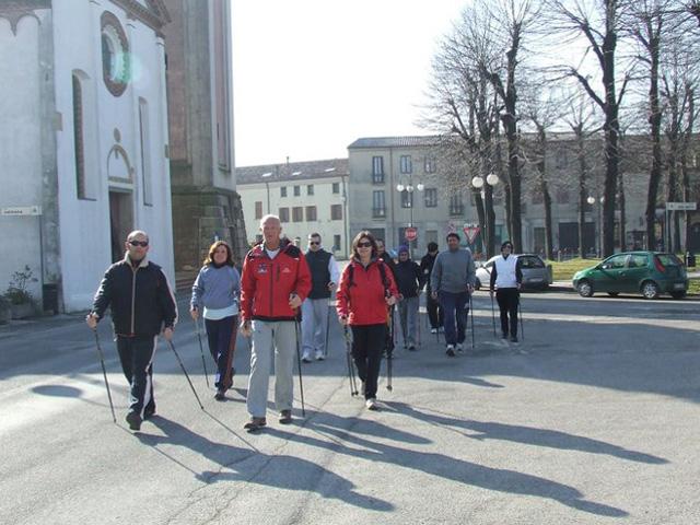 Gruppo di nordic walking in marcia lungo una strada asfaltata