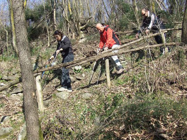 Tre partecipanti scendono lungo un ripido ed accidentato sentiero
