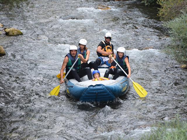 su un gommone si trovano quattro persone ed un bambino tutti protetti con caso e giubbotto che fanno la discesa di un fiume