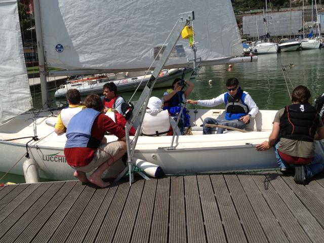 persone sedute sulla barca a vela ancora sul molo, pronti per partire