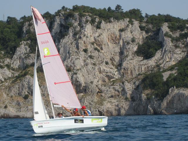 Barca a vela in navigazione lungo una costa rocciosa