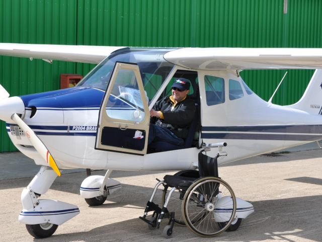 Un pilota disabile mentre si prepara a scendere dal suo aereo alla sua carrozzina