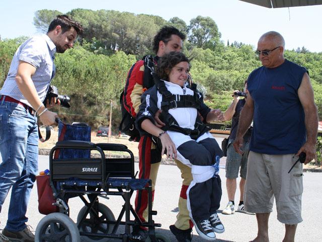 persona con disabilità motoria viene preparata con l'attrezzatura necessaria per poi lanciarsi con il paracadute