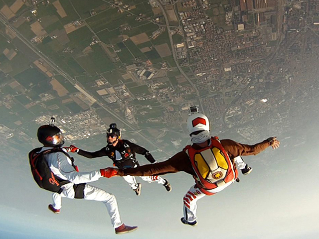 Formazione di tre paracadutisti che si tengono per mano mentre sono in caduta libera