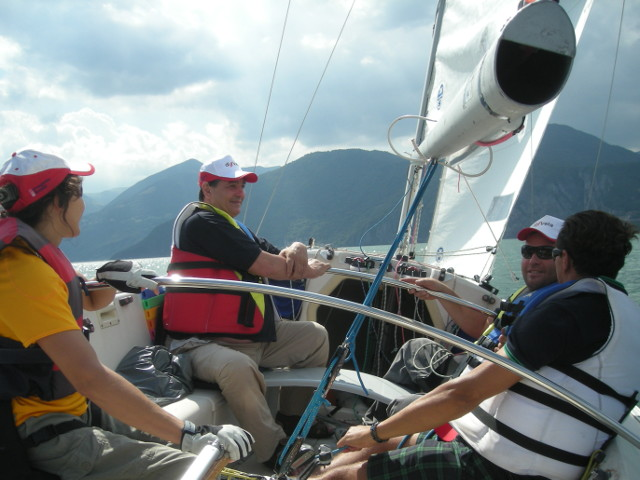 persone sorridenti sedute nella barca a vela che sta navigando