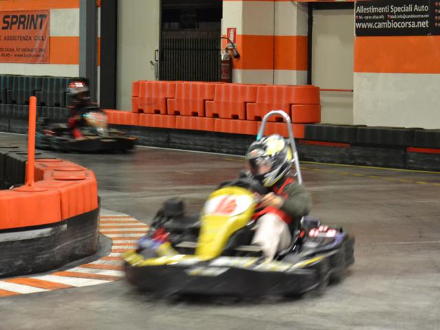 un pilota a bordo di un go kart affronta una curva e lo segue un altro pilota