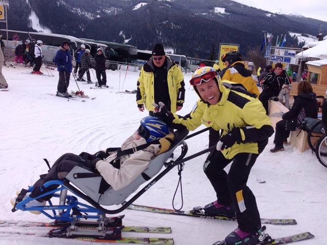 il maestro e lo sciatore sono pronti per parteire, lo sciatore è seduto su una apposito usilio per sciare
