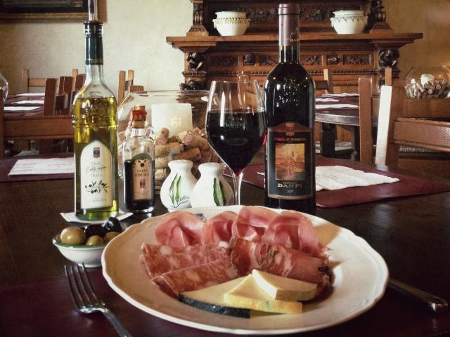 immagine in soggettiva di un piatto di salumi e formaggi con calice di vino rosso