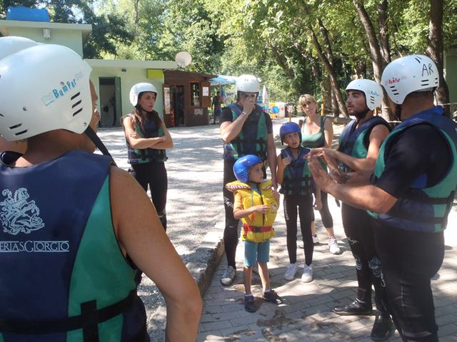 un istruttore spiega come si svolgerà la discesa del fiume in gommone a persone già pronte con casco e giubbotti salvagente
