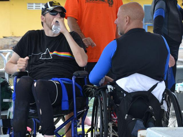 Due uomini in sedia a rotelle conversano dopo la lezione di sub