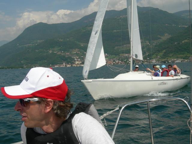 foto di una barca a vela con equipaggio scattata da un'altra barca a vela che naviga sul lago