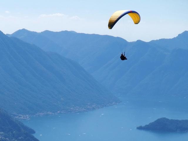 un parapendio in volo su un lago circondato da montagne