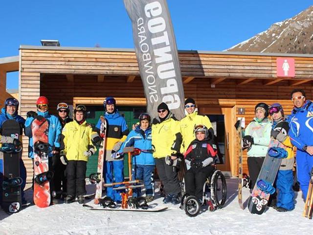 foto di gruppo sulla neve di maestri e sciatori con diverse attrezzature per sciare