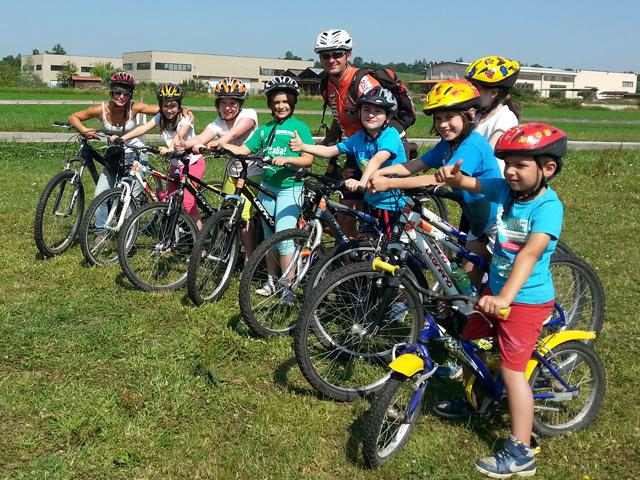 bambini sorridenti in posa in sella a delle biciclette