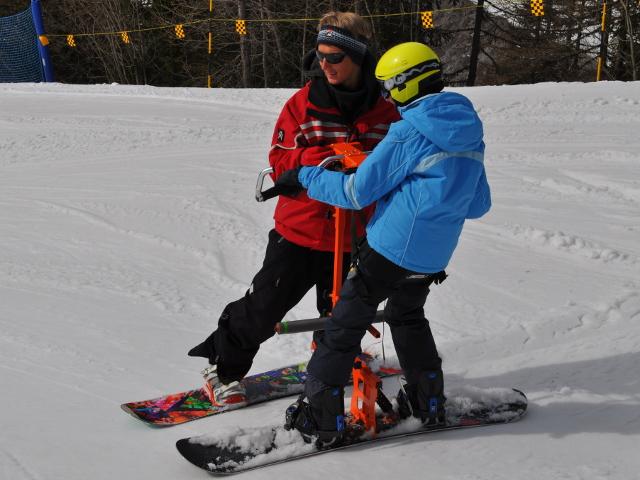 maestro e persona disabile che sciano grazie al BASS ovvero uno snowboard adattato che consente anche a persone con gravi disabilità di svolgere attività in stazione eretta