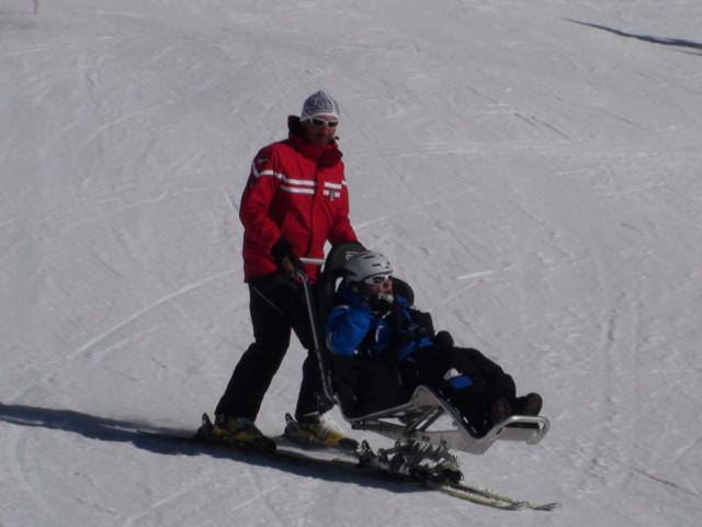 maestro e persona disabile che sciano insieme grazie ad un monosci
