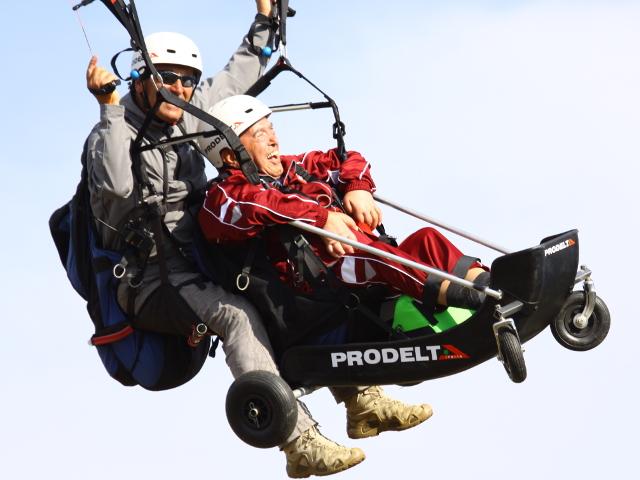 Istruttore e portatore di disabilità in volo con il parapendio
