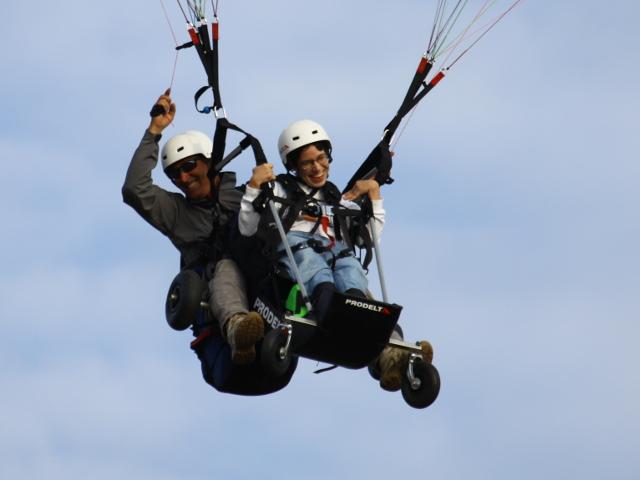 Istruttore e persona con disabilità volano in parapendio