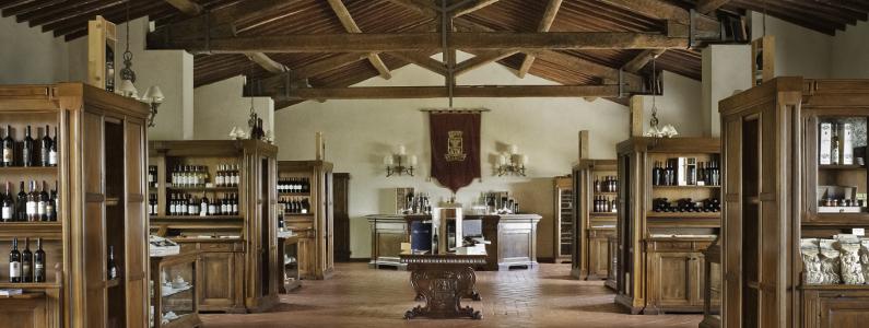sala del castello banfi in cui vengono esposte in scaffali di legno le bottiglie di vino prodotte