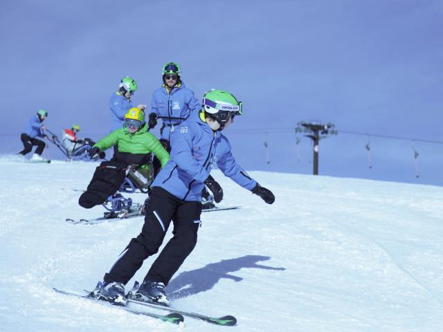 Sciatore disabile scende su monosci con istruttore