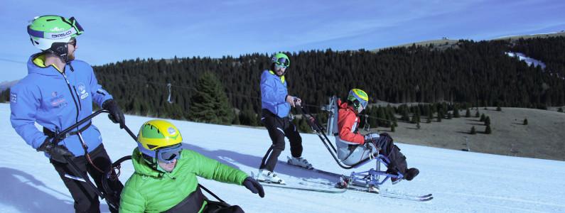 Due sciatori disabili su monosci scendono con gli istruttori