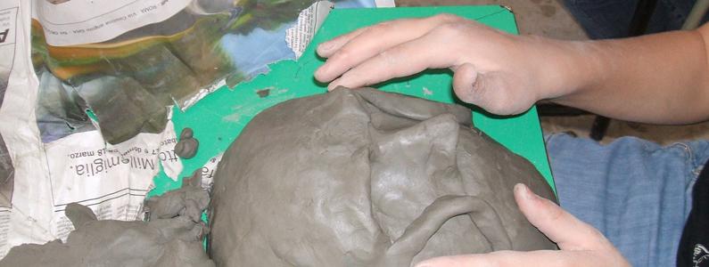Due mani modellano un volto di creta