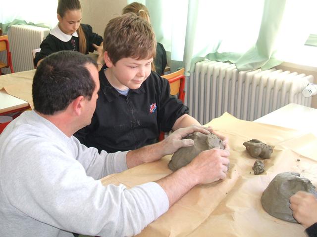 L'insegnante guida la mano di un bambino non vedente a modellare un pezzo di creta