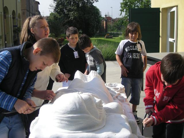 Bambini non vedenti esplorano con le mani la statua del Cristo Rivelato del Maestro Tagliaferri