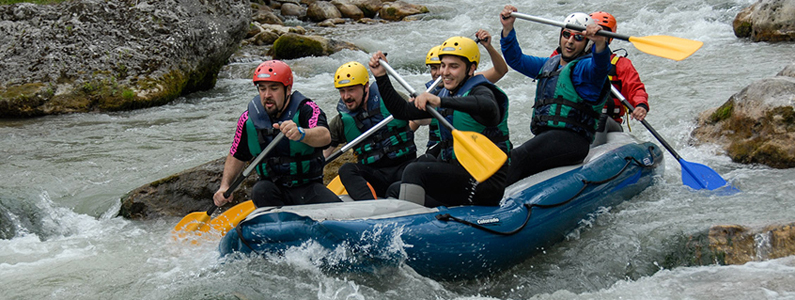sei parsone in gommone sfidano la corrente del fiume usando i loro remi