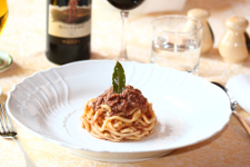 Piatto di spaghetti al ragù serviti a mò di tortino guarnito con una fogliolina d'alloro