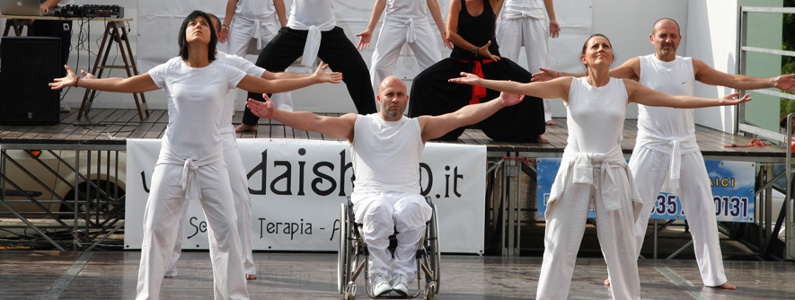 gruppo di persone, di cui una in sedia a ruote, tutte con le braccia tese, durante una dimostrazione di Dai Shi Do