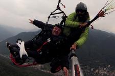 due persone in volo: un istruttore e una persona con disabilità motoria seduto su un'apposita struttura che si appende al parapendio