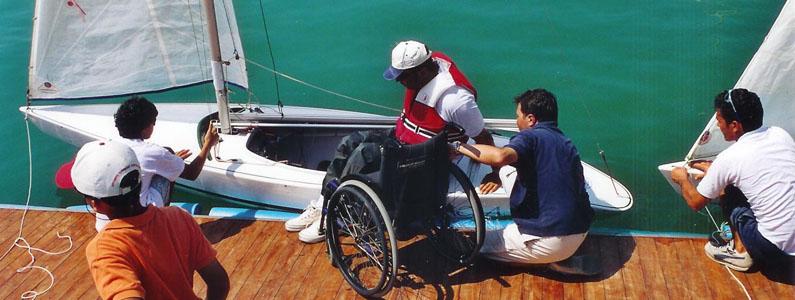posizionamento di una persona con disabilità motoria, dalla sedia a ruote alla barca a vela