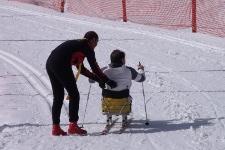istruttore affianca uno sciatore con disabilità motoria che percorre una pista da sci di fondo