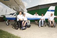 Quattro ragazzi in sedia a rotelle sono in posa con il loro istruttore di volo a fianco dell'aereo ultraleggero della scuola
