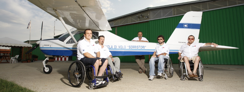 Quattro ragazzi in sedia a rotelle con il loro istruttore di volo a fianco dell'aereo ultraleggero della scuola