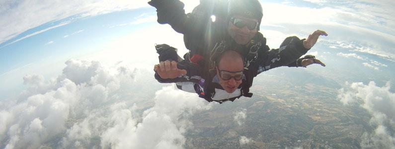 foto dei visi sorridenti di due persone che volano in tandem in un momento di caduta libera
