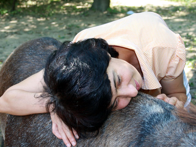 una donna sta appoggiata con la testa sul dorso di un asino