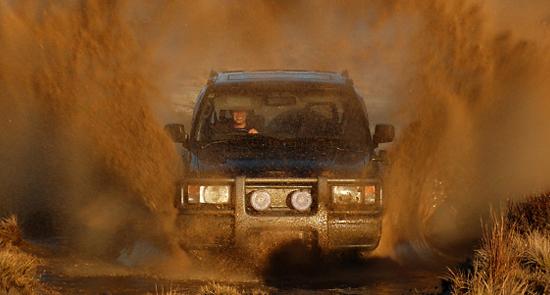 Fuoristrada coperto di fango che attraversa una pozza d'acqua